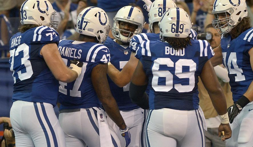 Indianapolis Colts quarterback Jacoby Brissett, center, is mobbed by teammates after he ran the ball into the end zone to score a touchdown during an NFL football game against the Cleveland Browns, Sunday, Sept. 24, 2017, in Indianapolis. (Joseph C. Garza/The Tribune-Star via AP)