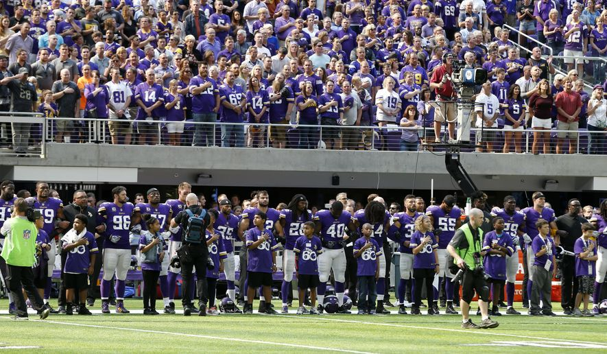 Minnesota Vikings players lock arms during the playing of the national anthem before an NFL football game against the Tampa Bay Buccaneers, Sunday, Sept. 24, 2017, in Minneapolis. (AP Photo/Jim Mone)
