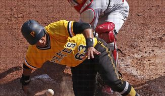 Pittsburgh Pirates' Chris Bostick (63) scores on a sacrifice fly to right field by Pirates' Elias Diaz as St. Louis Cardinals catcher Carson Kelly drops the ball in the third inning of a baseball game, Sunday, Sept. 24, 2017 in Pittsburgh. (AP Photo/Gene J. Puskar)