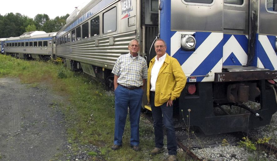 In this Sept. 5, 2017 photo, David Blittersdorf, right, and Charlie Moore pose in Barre, Vt., in front of one of a dozen passenger rail cars Blittersdorf bought to try to jump-start a commuter rail system in Vermont. Moore, a long-time rail expert in the state, is working to make that happen. (AP Photo/Wilson Ring)