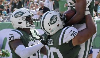 New York Jets running back Bilal Powell (29) celebrates with teammates Dakota Dozier (70) and Lawrence Thomas (97) during the second half of an NFL football game against the Miami Dolphins, Sunday, Sept. 24, 2017, in East Rutherford, N.J. (AP Photo/Bill Kostroun)