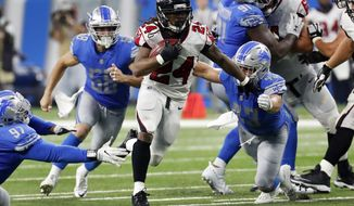 Atlanta Falcons running back Devonta Freeman (24) rushes through the Detroit Lions defense during the first half of an NFL football game, Sunday, Sept. 24, 2017, in Detroit. (AP Photo/Rick Osentoski)