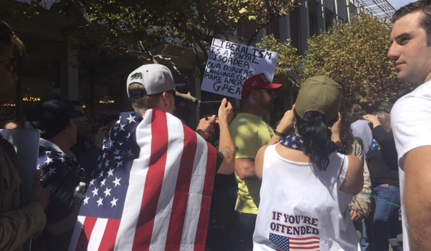 Pro-first amendment supporters rally at UC Berkeley's Sproul Plaza before right-wing provocateur Milo Yiannopoulos made a brief appearance on campus in Berkeley, Calif., Sunday, Sept. 24, 2017. Yiannopoulos was whisked away in a car after a brief appearance at the University of California, Berkeley that drew a few dozen supporters and a slightly larger crowd protesting the Yiannopoulos.  (AP Photo/Daisy Nguyen)