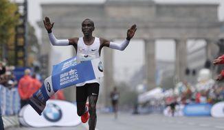 Kenya's Eliud Kipchoge crosses the line to win the 44th Berlin marathon in Berlin, Germany, Sunday, Sept. 24, 2017. (AP Photo/Michael Sohn)