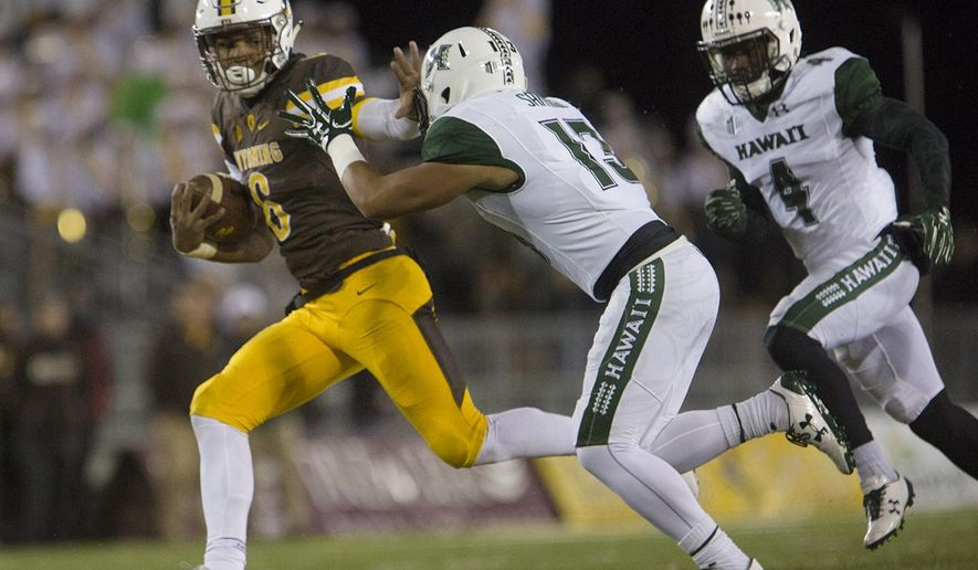Wyoming running back Trey Woods (6) makes a run for the end zone as Hawaii defensive Back Keala Santiago (13) chases him during an NCAA college football game Saturday, Sept. 23, 2017, in Laramie, Wyo. (Josh Galemore/The Casper Star-Tribune via AP)