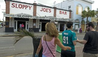In this photo provided by the Florida Keys News Bureau, cruise ship tourists walk past Sloppy Joe's Bar Sunday, Sept. 24, 2017, in Key West, Fla. The arrival of Royal Caribbean's Empress of the Seas arrival was the first time a cruise ship has docked in Key West since prior to Hurricane Irma's passage through the Florida Keys. (Rob O'Neal/Florida Keys News Bureau via AP)