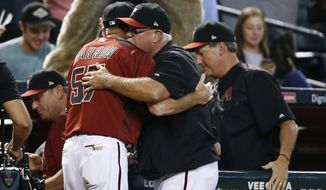 Arizona Diamondbacks manager Torey Lovullo, left, Reno Aces manager Jerry Narron (57), pitching coach Mike Butcher, second from right, and hitting coach Dave Magadan, right, congratulate one another after it was announced the Diamondbacks clinched a playoff spot during the fourth inning of a baseball game against the Miami Marlins, Sunday, Sept. 24, 2017, in Phoenix. Both the St. Louis Cardinals and Milwaukee Brewers lost their games, giving the Diamondbacks their National League Wild Card playoff spot. (AP Photo/Ross D. Franklin)