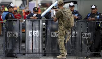 In this Sept. 22, 2017 photo, a civilian dressed in fatigues passes out chocolate to police guarding the site of an office building that collapsed during Tuesday's 7.1 earthquake, as search and rescue operations continue there at the corner of Oaxaca and Alvaro Obregon streets in the Roma Norte neighborhood in Mexico City. As rescue operations stretched into Day 5, residents throughout the capital have held out hope that dozens still missing might be found alive. (AP Photo/Gustavo Martinez Contreras)