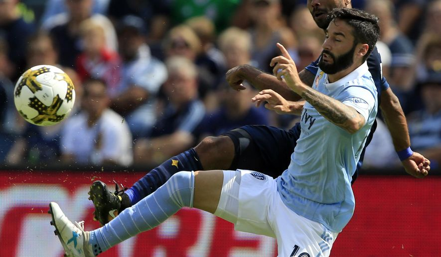 Sporting Kansas City forward Cristian Lobato (19) plays the ball against Los Angeles Galaxy defender Ashley Cole, back, during the first half of an MLS soccer match in Kansas City, Kan., Sunday, Sept. 24, 2017. (AP Photo/Orlin Wagner)