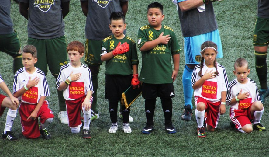 Five-year-old Derrick Tellez and his older brother Josue Tellez, right, take part in the national anthem on field with the Portland Timbers before a soccer match against Orlando City on Sunday, Sept. 24, 2017, in Portland, Ore. Derrick Tellez, a goalkeeper, was signed to a one-game contract with the Timbers as part of his wish with Make-A-Wish Oregon. (AP Photo/Anne M. Peterson)