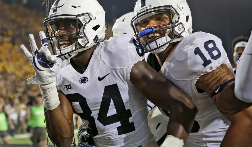 Penn State wide receiver Juwan Johnson, left, is congratulated by teammate Jonathan Holland after catching a touchdown pass as time expired to defeat Iowa in an NCAA college football game Saturday, Sept. 23, 2017, in Iowa City, Iowa. (AP Photo/Jeff Roberson)