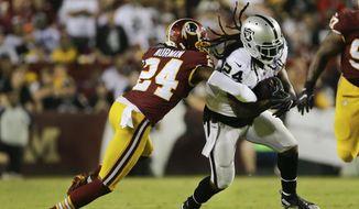 Washington Redskins cornerback Josh Norman, left, stops Oakland Raiders running back Marshawn Lynch (24) during the first half of an NFL football game in Landover, Md., Sunday, Sept. 24, 2017. (AP Photo/Mark Tenally)