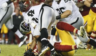 Oakland Raiders running back Marshawn Lynch (24) is stopped by Washington Redskins outside linebacker Preston Smith (94) during the first half of an NFL football game in Landover, Md., Sunday, Sept. 24, 2017. (AP Photo/Alex Brandon)