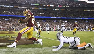 Washington Redskins running back Chris Thompson (25) carries the ball into the end zone for a touchdown as Oakland Raiders cornerback Gareon Conley (22) looks on during the first half of an NFL football game in Landover, Md., Sunday, Sept. 24, 2017. (AP Photo/Pablo Martinez Monsivais)