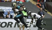 Jacksonville Jaguars tight end Marcedes Lewis, left, scores a touchdown past Baltimore Ravens strong safety Tony Jefferson during the second half of an NFL football game at Wembley Stadium in London, Sunday Sept. 24, 2017. (AP Photo/Matt Dunham)