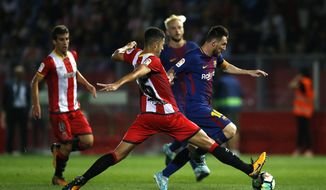 FC Barcelona's Lionel Messi, right, duels for the ball against Girona's Juanpe Ramirez during the Spanish La Liga soccer match between Girona and FC Barcelona at the Montilivi stadium in Girona, Spain, Saturday, Sept. 23, 2017. (AP Photo/Manu Fernandez)