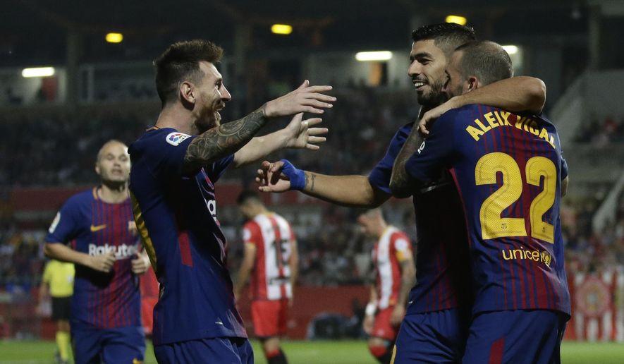 FC Barcelona's Lionel Messi, Luis Suarez, center, and Aleix Vidal celebrate a goal during the Spanish La Liga soccer match between Girona and FC Barcelona at the Montilivi stadium in Girona, Spain, Saturday, Sept. 23, 2017. (AP Photo/Manu Fernandez)