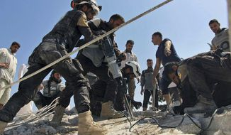 This photo provided by the Syrian Civil Defense White Helmets, which has been authenticated based on its contents and other AP reporting, shows Civil Defense workers using machinery to search through the rubble after airstrikes hit in Khan Sheikhoun, in the northern province of Idlib, Syria, Sunday, Sept, 24, 2017. The Syrian Observatory for Human Rights, a Syrian war monitoring group says airstrikes have targeted rural Aleppo for the first time in months since a cease-fire took hold in the province. (Syrian Civil Defense White Helmets via AP)