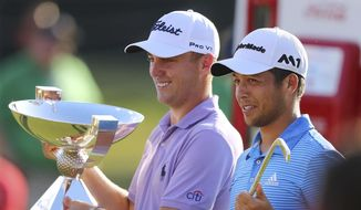 Justin Thomas, left, holds the trophy after winning the Fedex Cup, as he stands with Xander Schauffele who holds the trophy after winning the Tour Championship golf tournament at East Lake Golf Club in Atlanta, Sunday, Sept. 24, 2017, in Atlanta. (Curtis Compton/Atlanta Journal-Constitution via AP)
