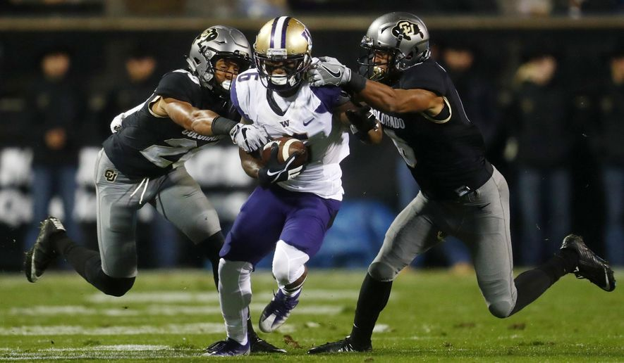 Washington wide receiver Chico McClatcher, center, is stopped by Colorado defensive backs Isaiah Oliver and Evan Worthington, right, during the first half of an NCAA college football game Saturday, Sept. 23, 2017, in Boulder, Colo. (AP Photo/David Zalubowski)
