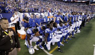 Members of the Indianapolis Colts take a knee during the nation anthem before an NFL football game against the Cleveland Browns. (Associated Press)