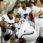 members of the Oakland Raiders take a knee while others stand during the national anthem.           Associated Press photo
