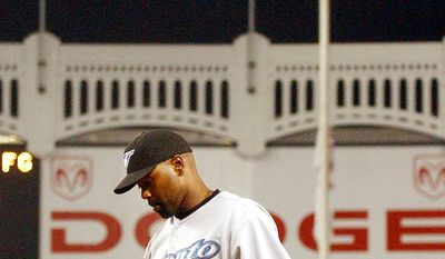 "Fervently anti-war, Carlos Delgado quietly carried out his personal protest, refusing to stand when ""God Bless America"" was played at ballparks across the majors. Delgado left the game after the sixth inning. (AP Photo/Frank Franklin II)"