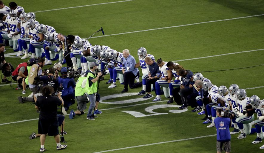 The Dallas Cowboys, led by owner Jerry Jones, center, take a knee prior to the national anthem prior to an NFL football game against the Arizona Cardinals.