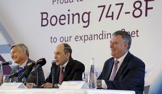Qatar Airways CEO Akbar Al Baker, center, speaks during a news conference with Boeing CEO Kevin McAllister, right, and Boeing vice chairman Ray Conner following a news conference before a delivery ceremony for a new Boeing 747-8 freighter to Qatar Airways Monday, Sept. 25, 2017, at Boeing's delivery center in Everett, Wash. The airline will also be taking delivery of one more 747-8, and Al Baker also announced Monday an order with Boeing for another four 777-300ERs. (AP Photo/Elaine Thompson)