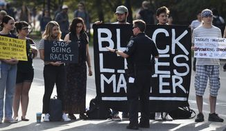A member of University of Michigan police speaks to allies of University of Michigan black students as they block the street in Ann Arbor, Mich., on Monday, Sept. 25, 2017. Students blocked the street as part of a planned weeklong protest against racism. (Melanie Maxwell/The Ann Arbor News via AP) ** FILE **