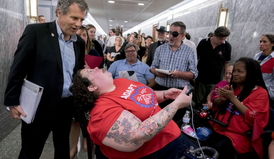 Sen. Sherrod Brown, D-Ohio, greet protesters outside a hearing room where the Senate Finance Committee will hold a hearing to consider the Graham-Cassidy healthcare proposal, on Capitol Hill, Monday, Sept. 25, 2017, in Washington. (AP Photo/Andrew Harnik)
