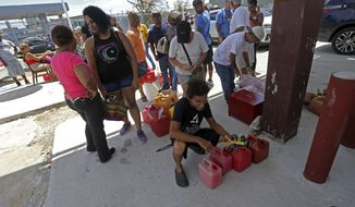 People line up with gas cans to get fuel form a gas station, in the aftermath of Hurricane Maria, in San Juan, Puerto Rico, Monday, Sept. 25, 2017. The U.S. ramped up its response Monday to the humanitarian crisis in Puerto Rico while the Trump administration sought to blunt criticism that its response to Hurricane Maria has fallen short of it efforts in Texas and Florida after the recent hurricanes there. (AP Photo/Gerald Herbert)