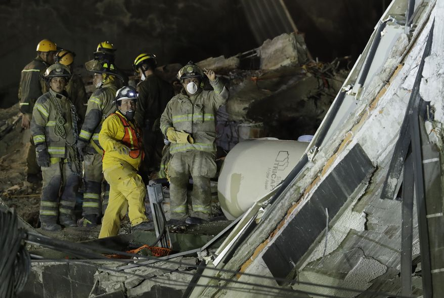 Rescue workers gesture as they work removing rubble in hopes of reaching dozens of people believed to be trapped inside a collapsed office building since a 7.1 magnitude earthquake, in the Roma Norte neighborhood of Mexico City, just after midnight Monday, Sept. 25, 2017. Search teams are still digging in dangerous piles of rubble hoping against the odds to find survivors at collapsed buildings. (AP Photo/Rebecca Blackwell)