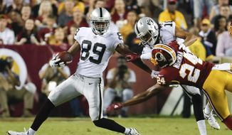 Washington Redskins cornerback Josh Norman (24) reaches for Oakland Raiders wide receiver Amari Cooper (89) during the first half of an NFL football game in Landover, Md., Sunday, Sept. 24, 2017. (AP Photo/Pablo Martinez Monsivais)