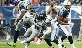 Tennessee Titans wide receiver Rishard Matthews (18) spins out of Seattle Seahawks strong safety Kam Chancellor's (31) tackle on his way to a touchdown during an NFL football game in Nashville, Tenn., Sunday, Sept. 24, 2017. The Titans won, 33-27. (Austin Anthony/Daily News via AP)