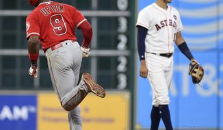 Los Angeles Angels' Justin Upton (9) rounds the bases after hitting a solo home run off Houston Astros relief pitcher Luke Gregerson, as shortstop Carlos Correa looks away during the eighth inning of a baseball game, Sunday, Sept. 24, 2017, in Houston. (AP Photo/Eric Christian Smith)