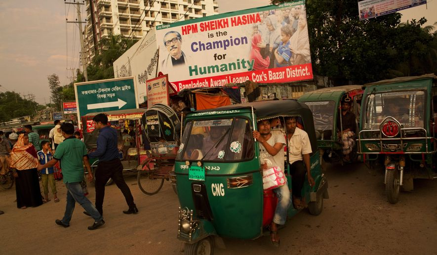 In this Saturday, Sept. 23, 2017 photo, Bangladeshis crowd an tuk-tuk on a street with a billboard in appreciation of Bangladesh's prime minister Sheikh Hasina for sheltering Rohingya Muslims fleeing Myanmar, in Cox's Bazar, Bangladesh. Vast areas in this coastal district are now entirely taken over by a sea of makeshift bamboo and plastic tents, homes for the more than 430,000 Rohingya Muslims who have fled here with stories of terrible persecution in Myanmar. The new arrivals spill out of the existing refugee camps for Rohingya Muslims that have existed in this border district since the 1990s. (AP Photo/Bernat Armangue)