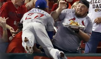 Chicago Cubs shortstop Addison Russell dives into the crowd but is unable to catch a foul ball hit by St. Louis Cardinals' Jedd Gyorko during the second inning of a baseball game Monday, Sept. 25, 2017, in St. Louis. (AP Photo/Jeff Roberson)
