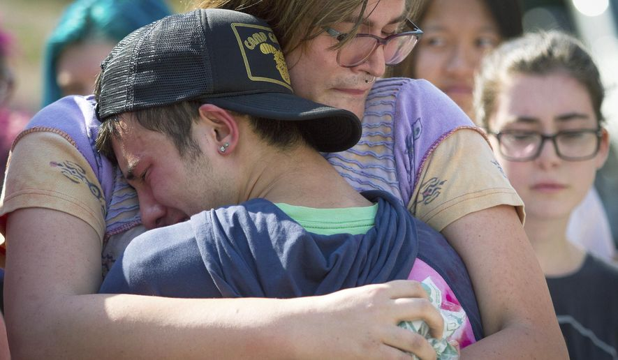 In this Sept. 17, 2017, photo, mourners hug at a memorial for Georgia Tech student Scout Schultz in Atlanta, Ga. Schultz was a 21-year-old who was shot and killed during a confrontation with police on campus Saturday, Sept. 16. (Steve Schaefer/Atlanta Journal-Constitution via AP)