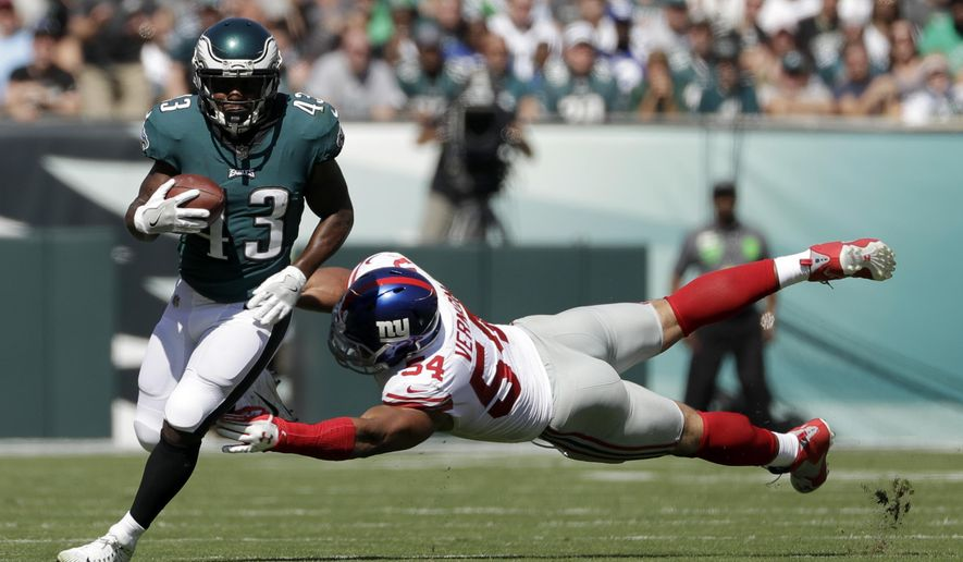 Philadelphia Eagles' Darren Sproles, left, tries to slip past New York Giants' Olivier Vernon during the first half of an NFL football game, Sunday, Sept. 24, 2017, in Philadelphia. (AP Photo/Michael Perez)