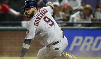 Houston Astros' Marwin Gonzalez (9) looks behind him after scoring on a sacrifice fly by Alex Bregman during the fourth inning against the Texas Rangers in a baseball game Monday, Sept. 25, 2017, in Arlington, Texas. (AP Photo/Richard W. Rodriguez)