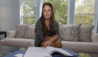 Former Word of Faith Fellowship church member Rachael Bryant poses for a photo with her tax records at her home in Charlotte, N.C., Tuesday, Sept. 19, 2017. She and 10 other members of the evangelical North Carolina-based church say their leader, Jane Whaley, coerced congregants into filing false unemployment claims after the faltering economy threatened weekly tithes from church-affiliated companies. (AP Photo/Chuck Burton)