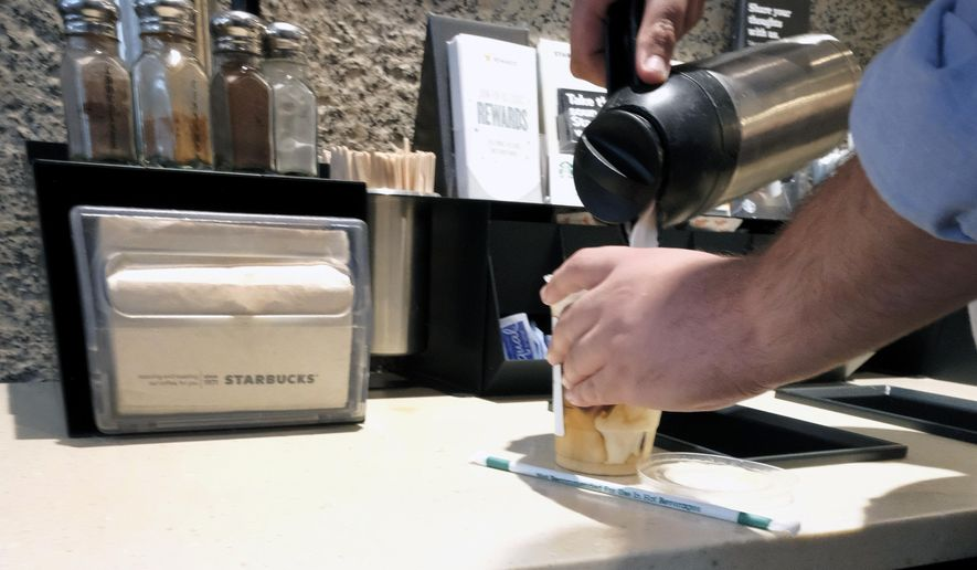 In this photo taken Friday, Sept. 22, 2017, a customer pours milk into coffee near a posted Proposition 65 warning sign at a Starbucks coffee shop in Los Angeles. In a long-running court case playing out in a Los Angeles courtroom, a nonprofit has been presenting evidence to show that coffee companies should post ominous warning labels about a cancer-causing chemical in every cup. (AP Photo/Richard Vogel)