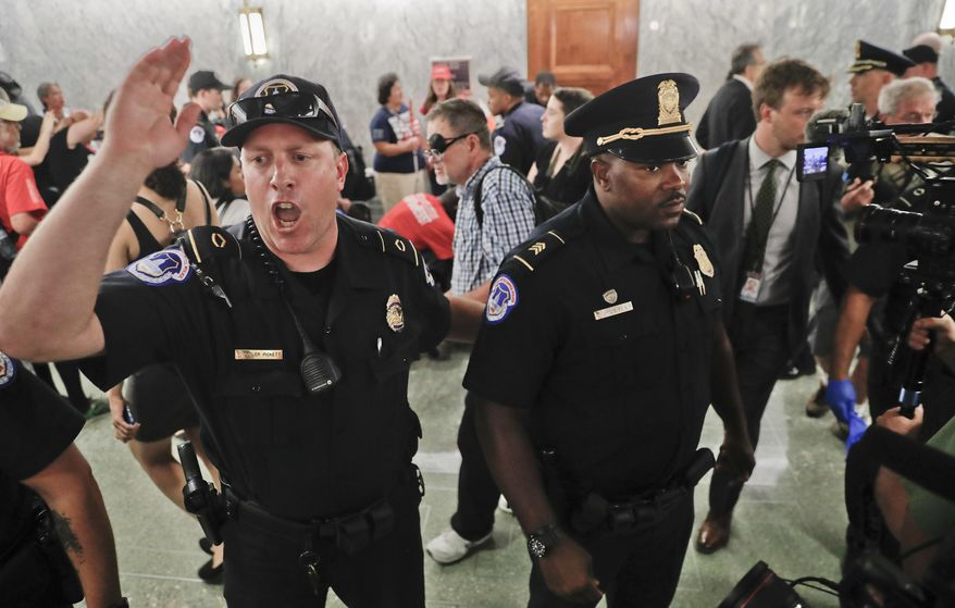 U.S. Capitol Police begin to clear the hallways in an effort to maintain order outside the Senate Finance Committee hearing on the last-ditch GOP push to overhaul the nation's health care system, on Capitol Hill in Washington, Monday, Sept. 25, 2017. (AP Photo/Pablo Martinez Monsivais)