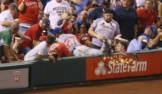 Chicago Cubs shortstop Addison Russell knocks over a fan's tray of nachos as he falls into the stands reaching for a foul ball hit by St. Louis Cardinals' Jedd Gyorko during the second inning of a baseball game Monday, Sept. 25, 2017, at Busch Stadium in St. Louis. Russell was unable to make the catch and Gyorko subsequently hit a solo home run. (Chris Lee/St. Louis Post-Dispatch via AP)