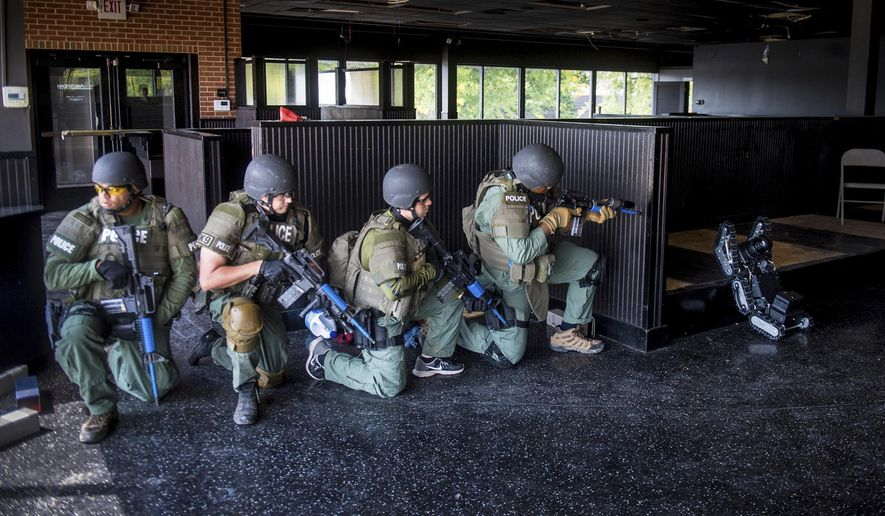 In this Sept. 5, 2017 photo, the Peoria Police Special Response Team runs training exercises  with a robotic unit from Transcend Robotics on the Riverfront Village platform in Peoria, Ill. The stair-climbing surveillance robot designed and built by Transcend, a California company that specializes in tactical equipment, has evolved with the input of officers on the Special Response Team (SRT) at the Peoria Police Department. (Fred Zwicky/Journal Star via AP)