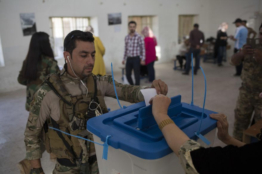 A Kurdish security guard casts his vote for independence in the city of Kirkuk, Monday Sept. 25, 2017. Iraq's Kurdish region vote in a referendum on whether to secede from Iraq. (AP Photo/Bram Janssen) ** FILE **