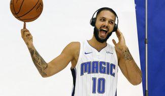 Orlando Magic's Evan Fournier pretends to listen to loud music on headphones while he spins a basketball as he poses for photos during Orlando Magic NBA basketball media day, Monday, Sept. 25, 2017, in Orlando, Fla. (AP Photo/John Raoux)