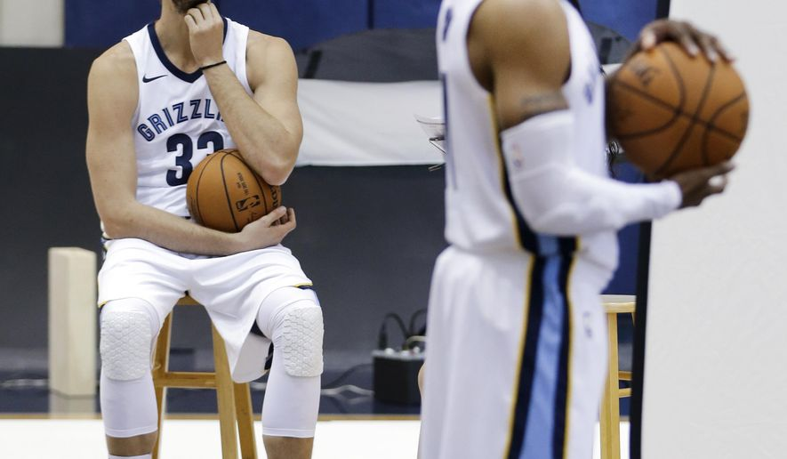 Memphis Grizzlies center Marc Gasol (33), of Spain, waits as guard Mike Conley poses for photos during the team's NBA basketball media day, Monday, Sept. 25, 2017, in Memphis, Tenn. With Zach Randolph and Tony Allen gone, the Grizzlies have revamped around Gasol and Conley. (AP Photo/Mark Humphrey)