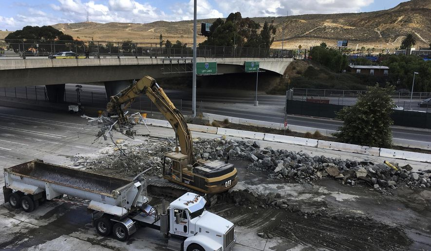 FILE - In this Saturday, Sept. 23, 2017, file photo, heavy machinery and construction crews works on California's Interstate 5 on the first day of a 57-hour closure of all Mexico-bound car traffic at the San Ysidro border crossing in San Diego, Calif. U.S. officials reopened the freeway lanes to Tijuana, Mexico early Monday, Sept. 25, at the U.S. border crossing ahead of schedule after a weekend shutdown for work on a $741 million expansion project. California Department of Transportation spokeswoman Caridad Sanchez said traffic began flowing again just after midnight. It connects San Diego to Tijuana. (AP Photo/Elliot Spagat, File)